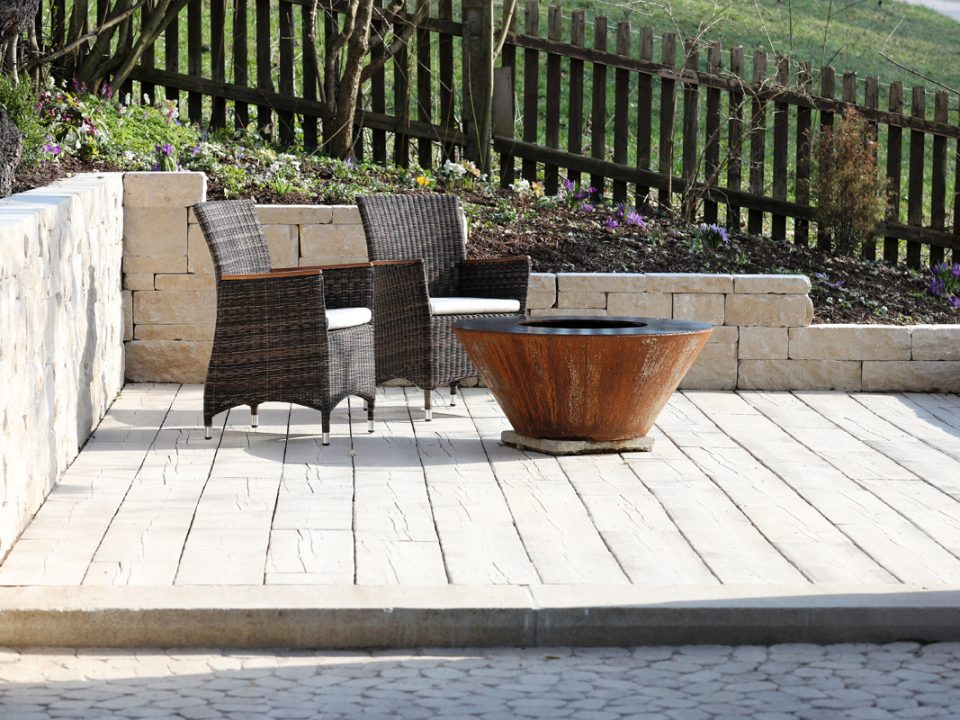 Erhöhter Sitzplatz mit Bodenbelag in Holzdielenoptik, eingefasst von Natursteinmauer